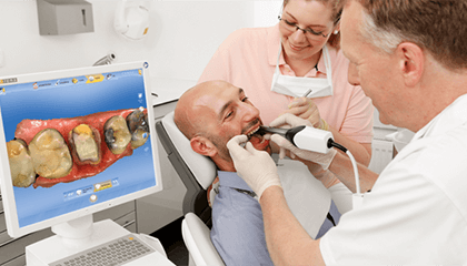 Dentist and assistant view damaged teeth on monitor