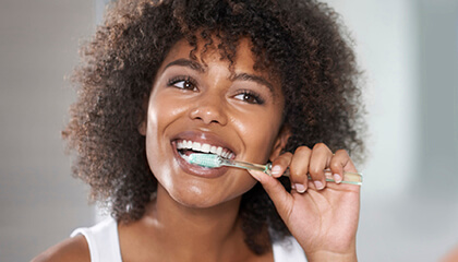 Female dental patient carefully brushing teeth