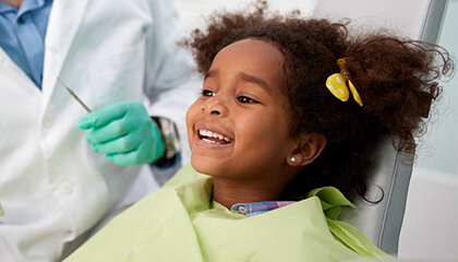 Young girl smiling happily in dental chair