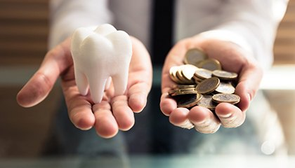 person holding a tooth and money in their hands