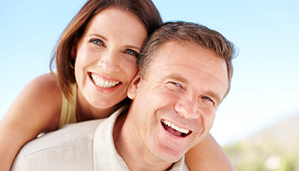 Older couple smiling broadly in sunshine