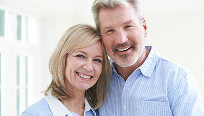 Older couple with healthy flawless smiles