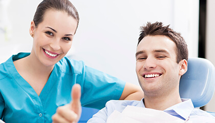 Male patient giving thumbs up in dental chair