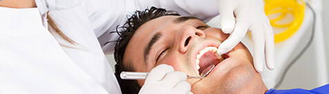 Male patient being treated in dental chair