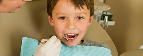 Young boy receiving treatment in dental chair