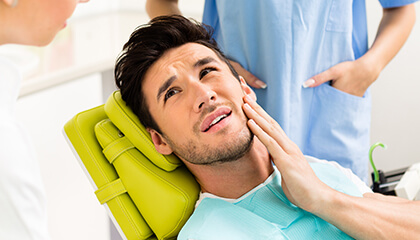 Male patient grimacing holding cheek in dental chair