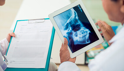Dentists looking at x-ray on tablet