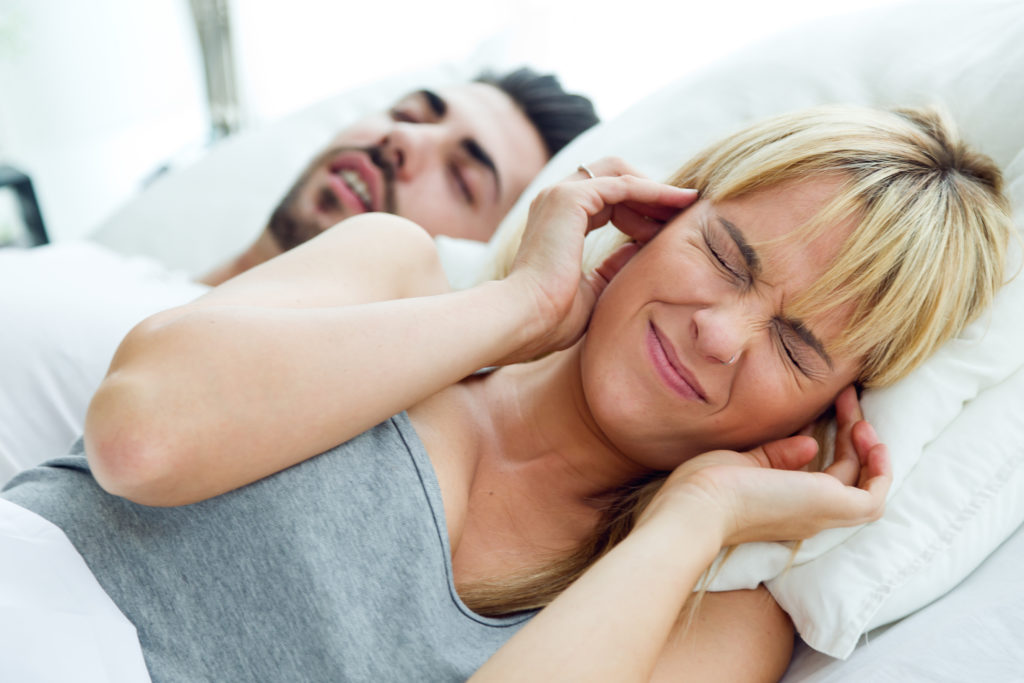 woman covering ears while partner snores