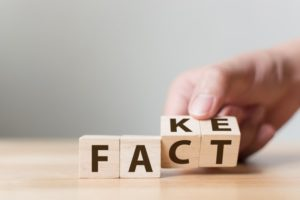 "letter blocks spelling out ""fact"" and ""fake"""