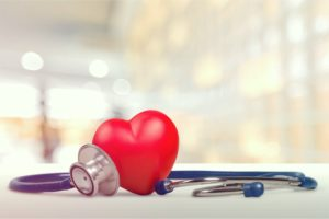 Red heart shape sitting on a table next to a stethoscope