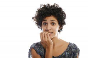Concerned woman biting her fingernails