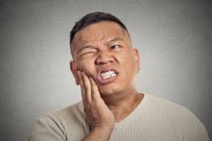 Pained man with hand on cheek needs his Melbourne emergency dentist