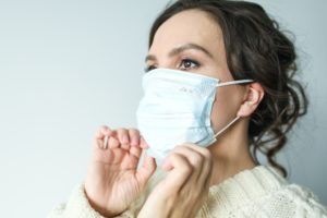 Woman putting on face mask before dentist in Melbourne.