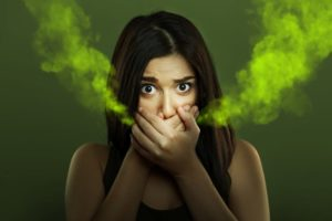 woman covering her mouth to stop bad breath