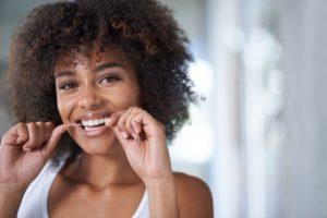 woman flossing to maintain healthy gums